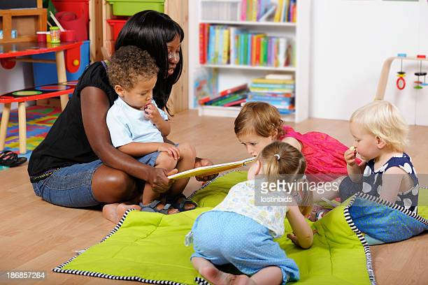 childminder/carer reading to a group of toddlers at nursery - manger stock photos and pictures