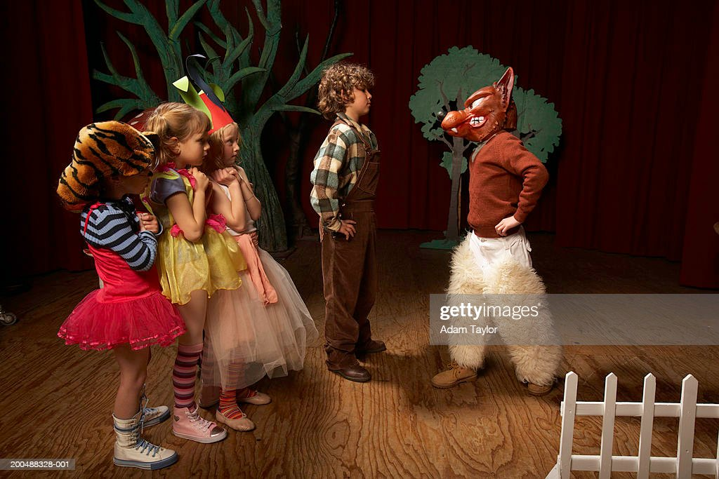Children (5-12) acting on stage, one boy confronting bad wolf : Stock Photo