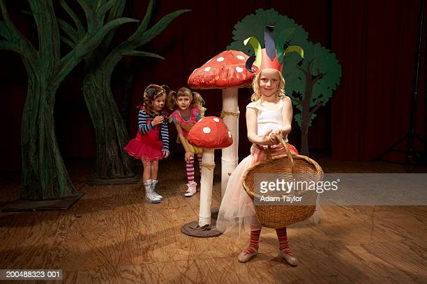 children (5-7) acting on stage, one girl holding basket, portrait - school play stock photos and pictures