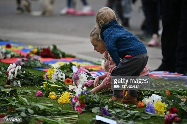 Children add flowers to tributes laid outside Windsor Castle, in Windsor, west of London, on April 9 following the announcement of the death of...