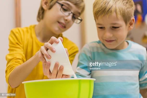 Children adding flour, baking