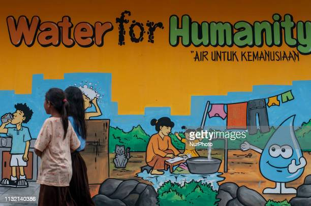 Children affected by a disaster passes in front of a water mural in the Duyu Temporary Shelter complex Palu Central Sulawesi Indonesia Saturday March...