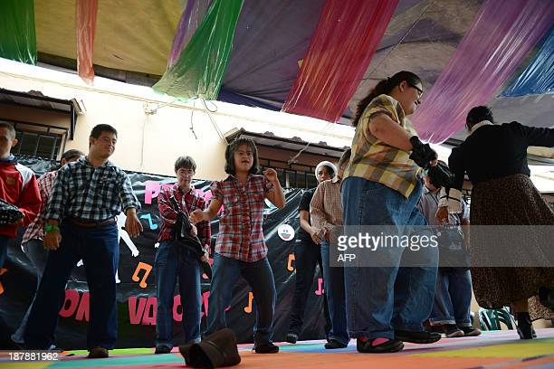 Children affected by the Down syndrome dance during the closing of the school year at Margarita Tejada fundation in Guatemala City on November 13...