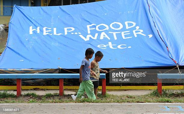 Children affected by the recent powerful earthquake walk past their temporary shelter with writings on the roof, asking fro help, at a school grounds...