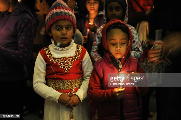 Children alongwith their parents hold candles during a candle light vigil for the victims Taliban attack in Peshawar on December 17 2014 in Noida...