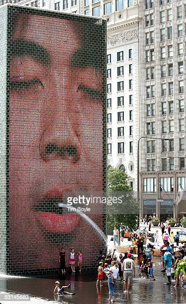Children and adults play in the water at Crown Fountain in Millennium Park June 24 2005 in Chicago Illinois With nearrecord high temperatures...