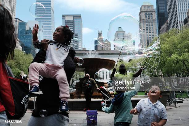 Children and adults play with bubbles in Bryant Park in Manhattan on May 04, 2021 in New York City. New York City, New Jersey and Connecticut have...