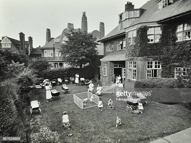 Children and carers in Wadham Gardens Hampstead London 1960 Women and children in the garden of a nursery with prams playpens and toys