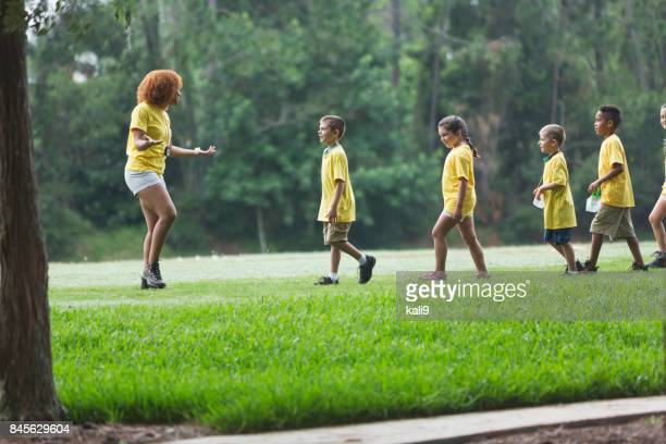 Children and counselor at summer camp in park