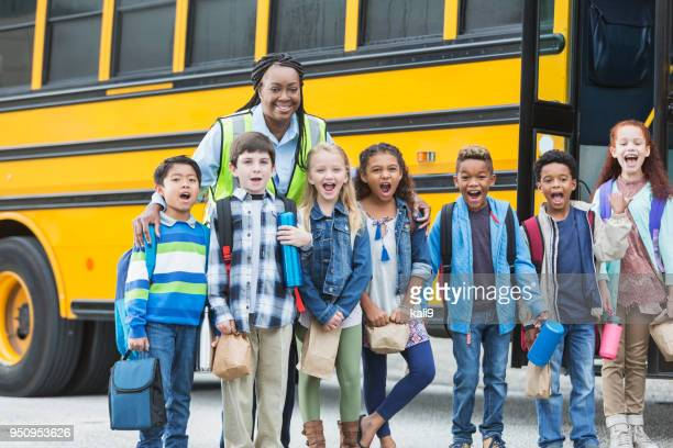 children and crossing guard standing outside school bus - field trip stock pictures, royalty-free photos & images