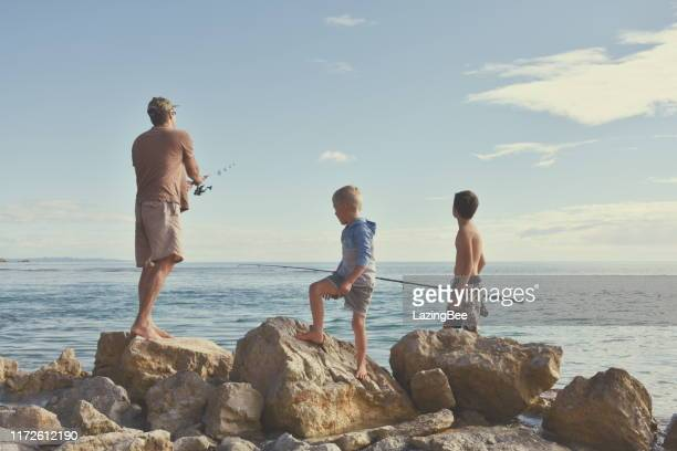 children and father fishing on coastal rocks - single father stock pictures, royalty-free photos & images