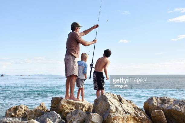 children and father fishing on coastal rocks - new zealand stock pictures, royalty-free photos & images
