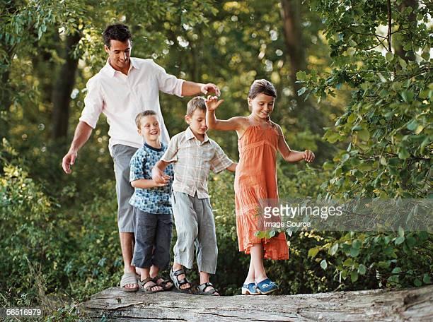 Vater und Kinder auf einem Baumstamm