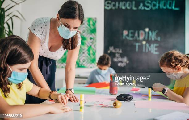 children and female teacher on class in private school classroom - teacher stock pictures, royalty-free photos & images