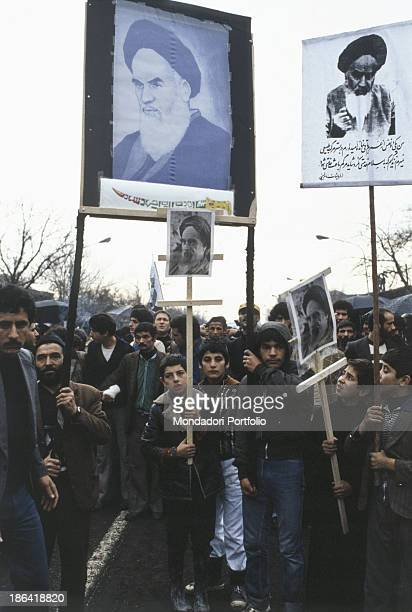 Children and men demonstrate during the Iranian revolution bringing banners with the images of Ruhollah Khomeyni The population protests against the...