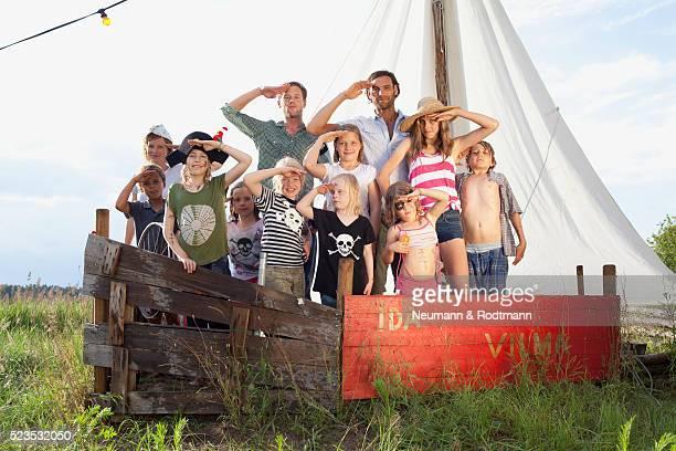Children (5-6, 7-9) and men in pirate costume saluting