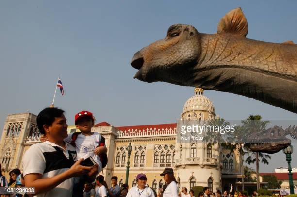 Children and parent stand next to a dinosaur statue during the Children's Day celebration at Government House in Bangkok Thailand on January 12 2019