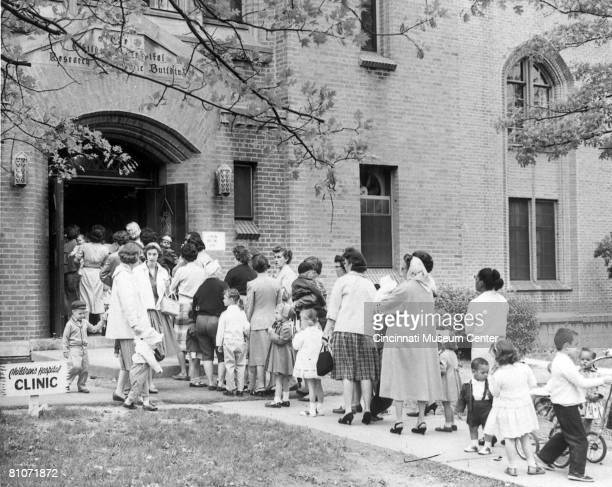 Children and parents line up outside the Children's Hospital to receive polio vaccines, Cincinnati, Ohio, April 24, 1960. The day marked to first day...