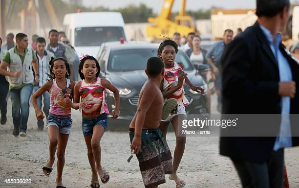 Children and security guards keep pace with a car carrying Brazil's President through the Complexo da Mare favela prior to a visit from President...