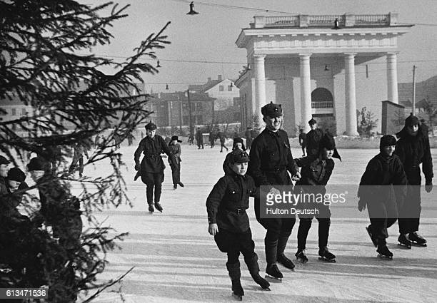 Children and soldiers take to the ice outside the main Red Army buildings in Moscow. January 1939.