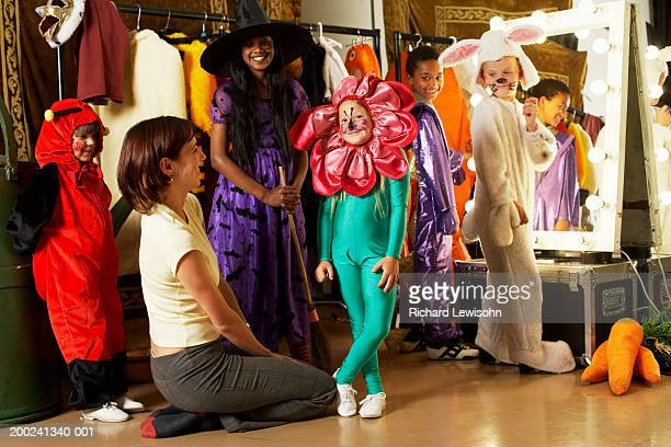 children (5-9) and teacher backstage, portrait of girl in flower costume - school play stock photos and pictures