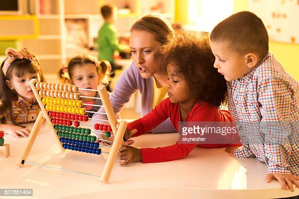 Children and teacher counting with abacus at preschool.