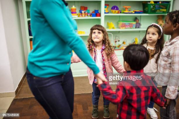 children and teacher playing together in classroom - childcare stock pictures, royalty-free photos & images