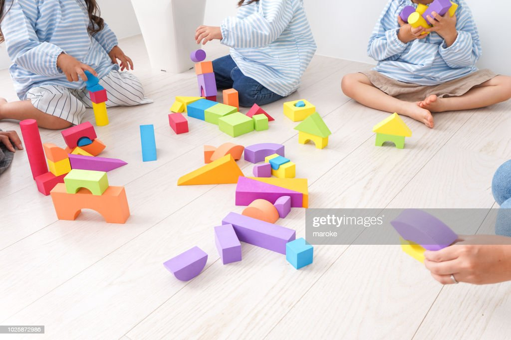 Children  and teacher playing with toy : Stock Photo