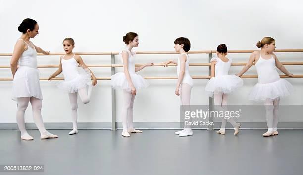 Children (9-13) and teacher resting at bar in ballet class