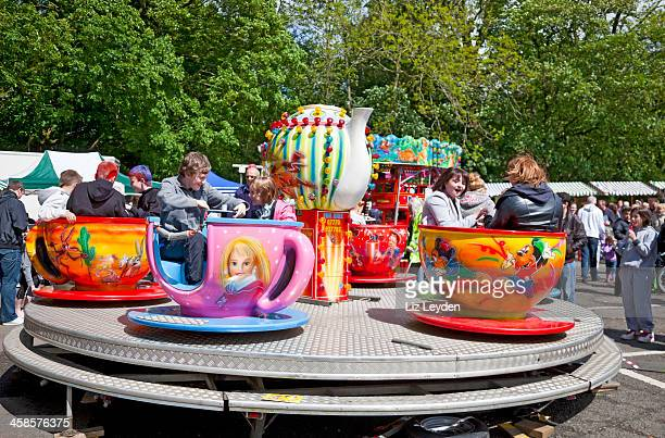 Children and teenagers on a teacups funfair ride