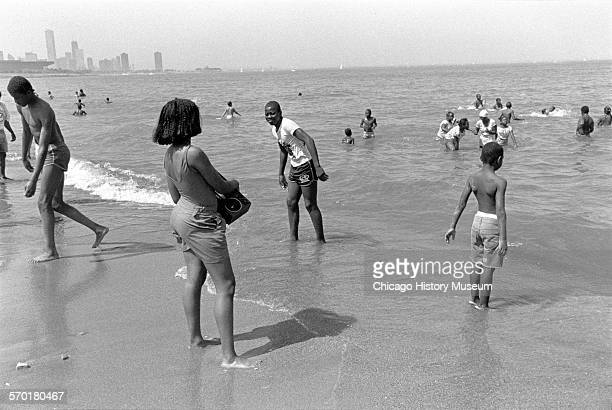 Children and teenagers swimming and playing at the 31st Street Beach Chicago Illinois circa 1987 A portion of the Chicago skyline is visible in the...