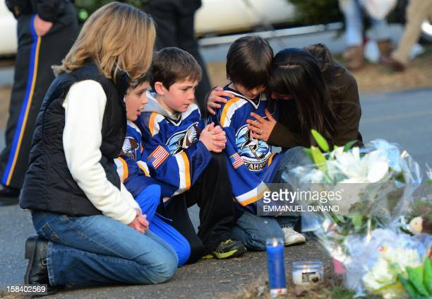 Children and their family pay tribute to the victims of an elementary school shooting in Newtown, Connecticut, on December 15, 2012. A young gunman...