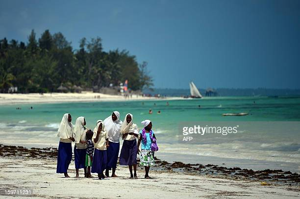 Children and their mothers walk on the beach after leaving school on January 8 2013 in Zanzibar AFP PHOTO / GABRIEL BOUYS