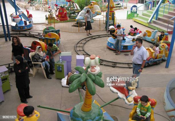 Children and their parents at a the playground in an amusement park on the Corniche in Beirut Lebanon 25th October 2008