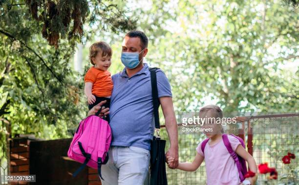 children and working father wearing face mask going to kindergarten - preschool stock pictures, royalty-free photos & images