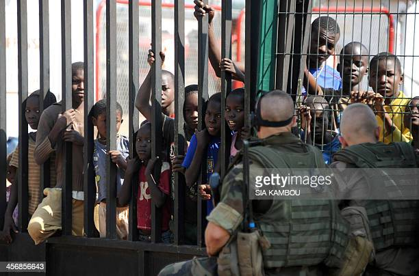 Children and young boys look on as French soldiers part of operation Sangaris stand guard on December 15 2013 near a gate at the airport in Bangui...