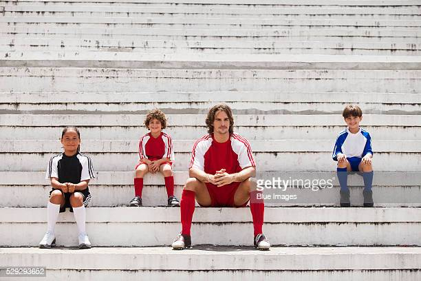 Children and young man sitting in empty soccer stadium