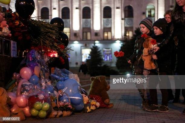 Children are about to lay flowers at a makeshift memorial in tribute to the victims of a Siberian shopping mall fire in Kemerovo in downtown...