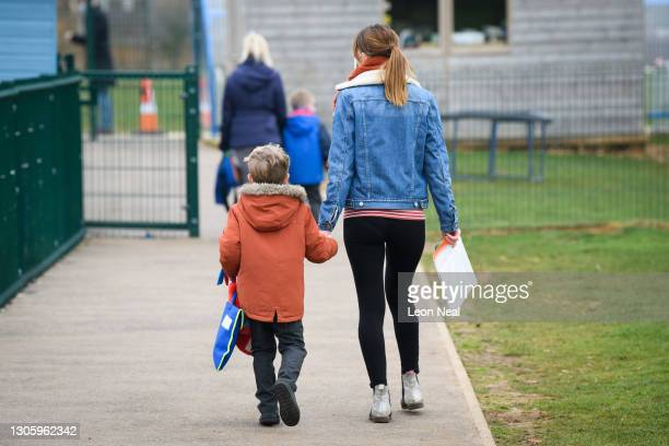 Children are escorted by their parents as classes return to Gamlingay Village Primary on March 08, 2021 near Bedford, United Kingdom. The school,...