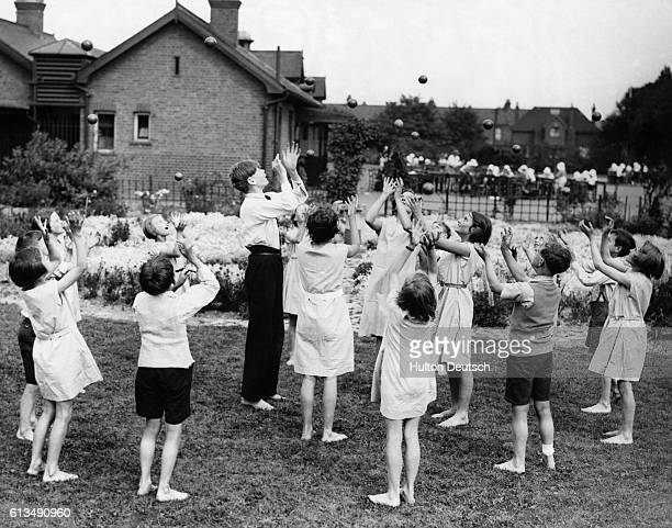 Children are given a lesson in juggling at the Benton Road Open Air School in Ilford England ca 1936 | Location Benton Road Open Air School Ilford...