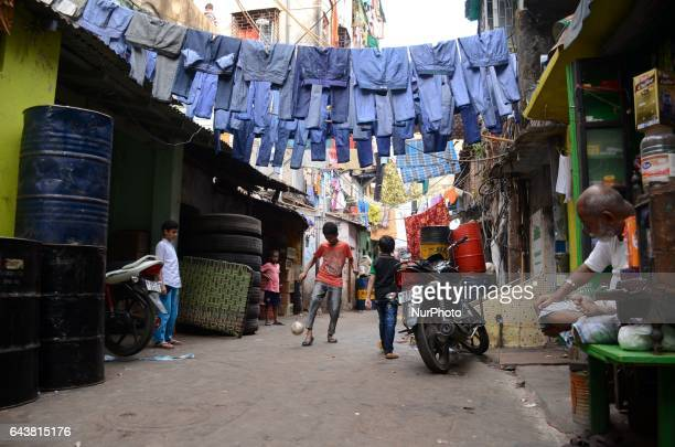 Children are playing football under hang to dry the used jeans pants in the street of slum area as they sold in second hand cloth market in Kolkata ,...