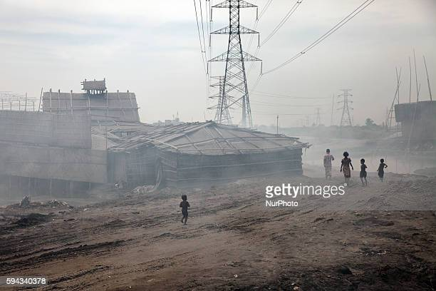 Children are playing in the filed Smoke from the factories covers the field in Dhaka Bangladesh on 22 August 2016 People from the southern part of...