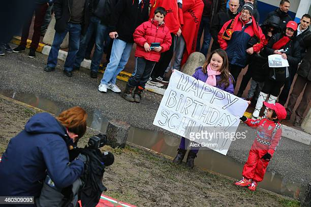 Children are put in front of the cameras as fans gather outside the Grenoble University Hospital Centre to mark the 45th birthday of former German...