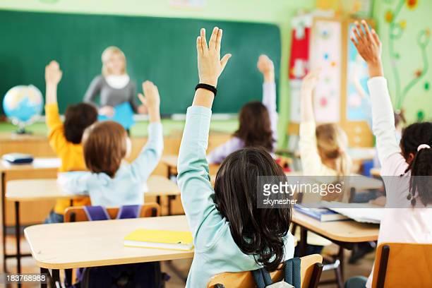 Les enfants sont soulevées mains dans une salle de classe.