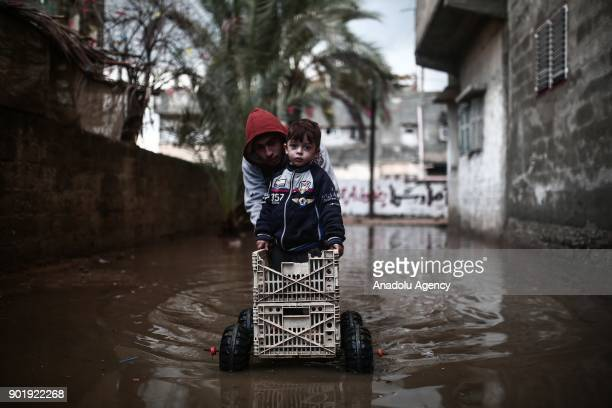 Children are seen at a mud covered road after heavy rainfall hit Rafah Gaza on January 06 2018