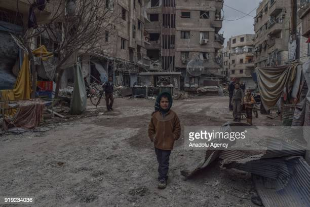 Children are seen at the debris of buildings after Assad Regime's airstrikes and ground attacks to Harasta town in the besieged Eastern Ghouta in...