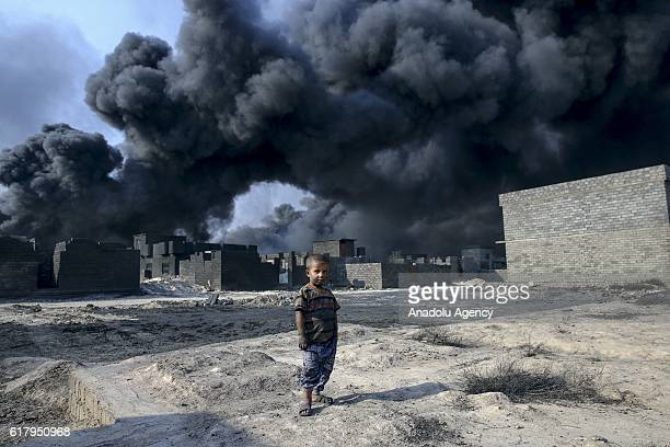 Children are seen at the street as smoke rise from oil wells, were set on fire by Daesh terrorists to limit coalition forces pilots' eyesight and to...