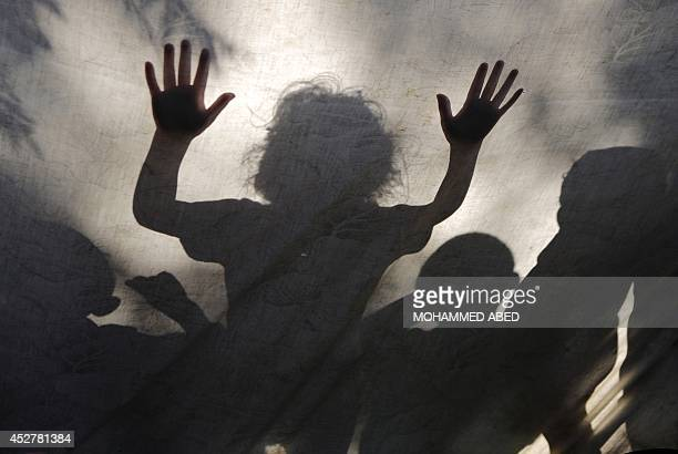 Children are seen behind a sheet which covers an improvised tent on July 27 2014 in the garden of AlShifa hospital in Gaza City where Palestinian...