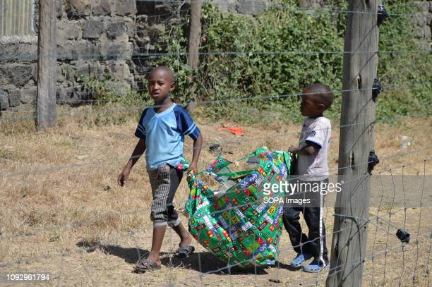 PARK NAKURU RIFTVALLEY KENYA Children are seen carrying a bag of garbage to the waiting truck during this year's World Wetlands Day in Lake Nakuru...