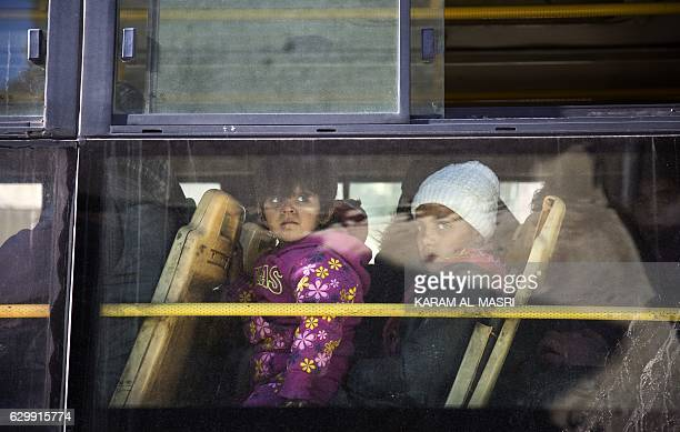 Children are seen inside a bus during an evacuation operation of rebel fighters and their families from rebelheld neighbourhoods in the embattled...